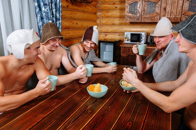 Five guys relax in the sauna after the steam room and drink tea