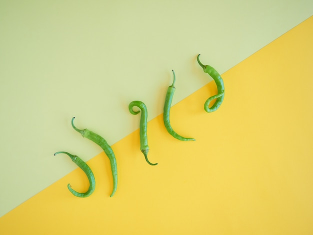 Five isolated green chili peppers on a simetrical vibran yelow surface