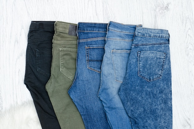 Five jeans on wooden table