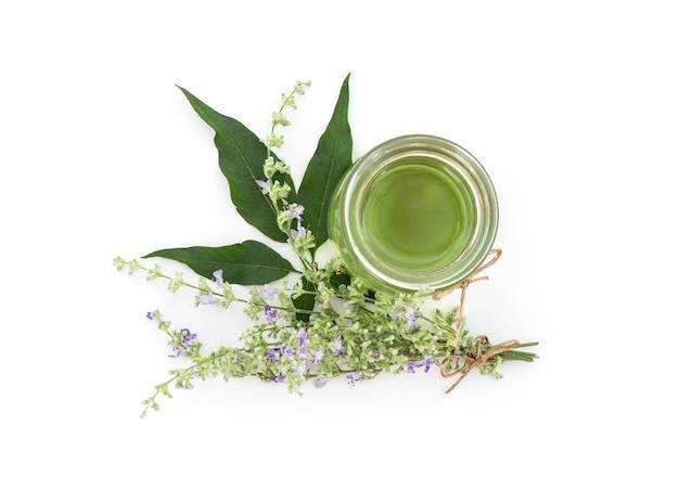 다섯 잎이 달린 순결한 나무 또는 vitex negundo 꽃과 흰색에 고립 된 병에 녹색 잎에서 기름을 추출