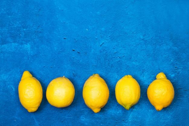 上面図のテクスチャードクラシックブルーの背景に5つのレモン