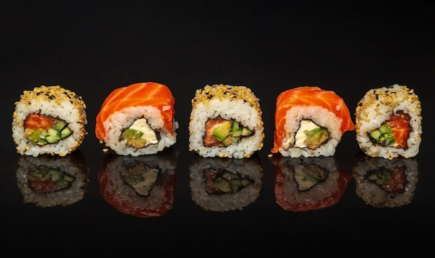 Five maki rolls in a row with salmon, avocado, tuna and cucumber