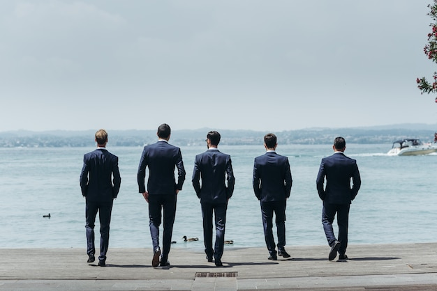 Five men in classy suits walk towards the blue sea