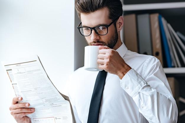 커피와 신선한 신문을 위한 5분. 사무실에 서 있는 동안 신문을 읽고 커피를 마시는 안경을 쓴 잘생긴 젊은 사업가