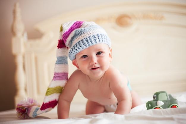 네 발에 크로셰 모자를 쓴 5개월 아기가 웃고 있습니다