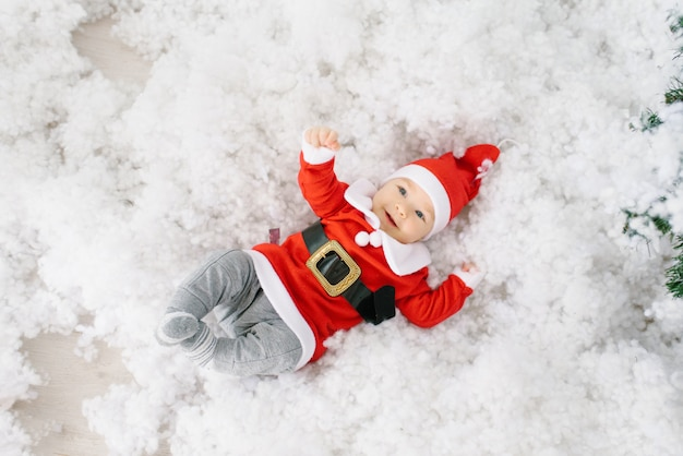 A five-month-old little child in a santa claus suit is lying in artificial snow on his back