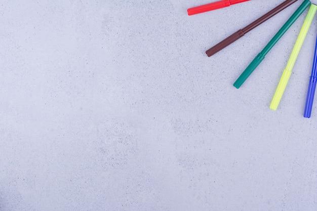 회색 표면에 고립 된 5 개의 여러 가지 빛깔의 젤 연필
