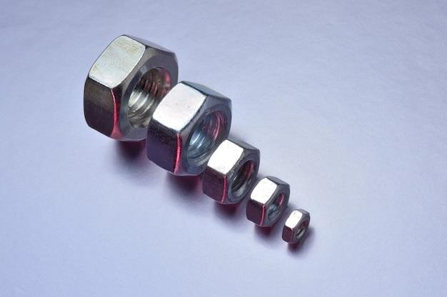 대형부터 소형까지 5개의 새로운 크롬 너트가 늘어서 있습니다. 금속 배경입니다. 확대.