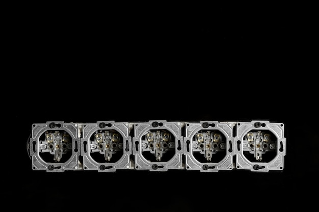 Five outlets in line, disassembled and mounted in black glass wall