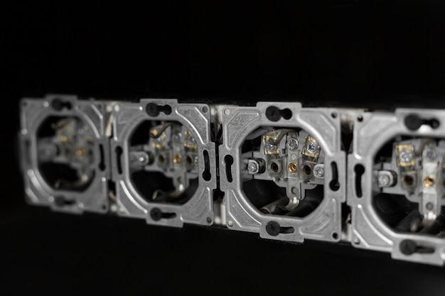 Five outlets in line, disassembled and mounted in black glass wall.