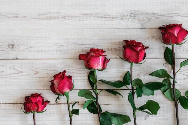 木製のテーブルの上に横になっている5つのピンクと赤のバラ