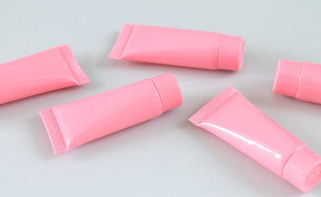 Пять розовых косметических трубок на сером крупном плане поверхности. дизайн контейнеров для спа-продуктов