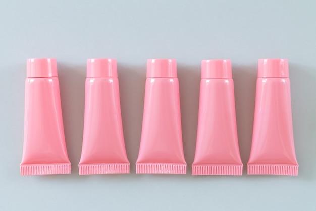 Вид сверху пять розовых косметических трубок на сером фоне. дизайн контейнеров для спа-продуктов