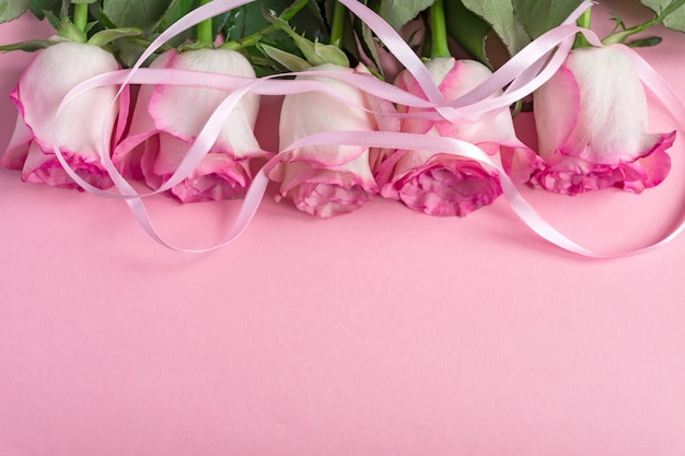 Five pink roses on pink with ribbon