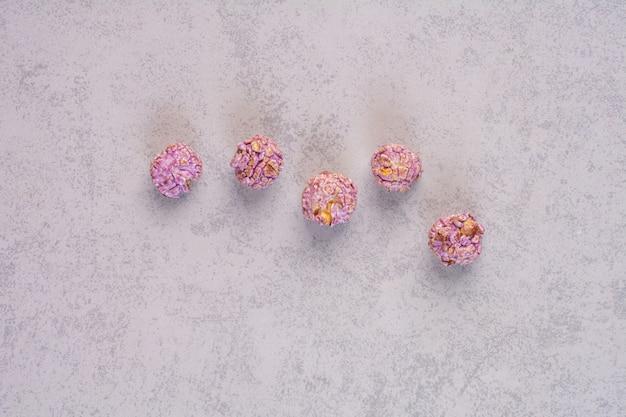 大理石の上に5つのポップコーンキャンディーが並んでいます。