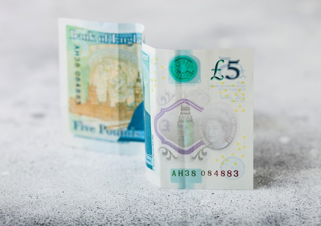 Five pounds banknote on light surface. world economy crisis concept.