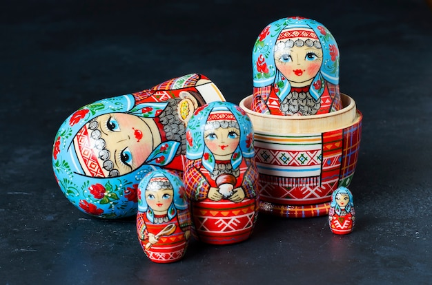 Пять красных матрешек. традиционная русская игрушка. черный бетонный фон