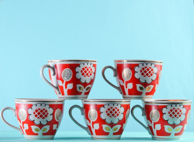 Five retro cups on a blue surface