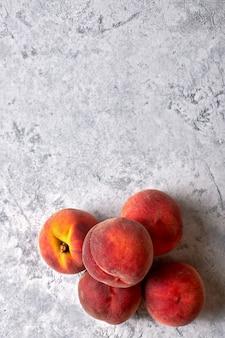 白い斑点を付けられた背景上の5つの熟したジューシーな桃