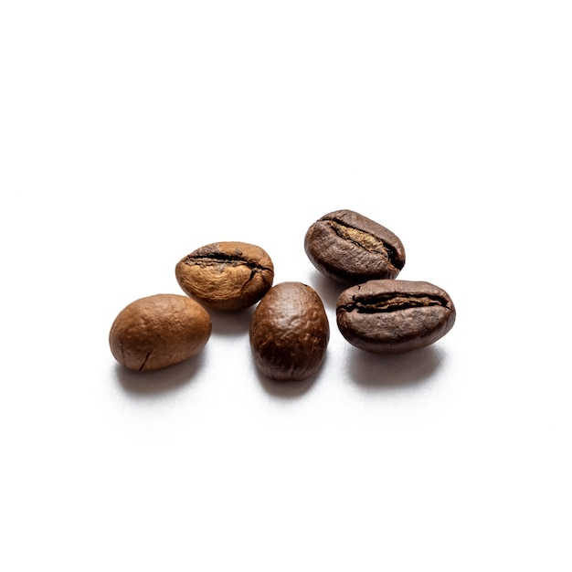 白い表面に散らばった5つの焙煎コーヒー豆