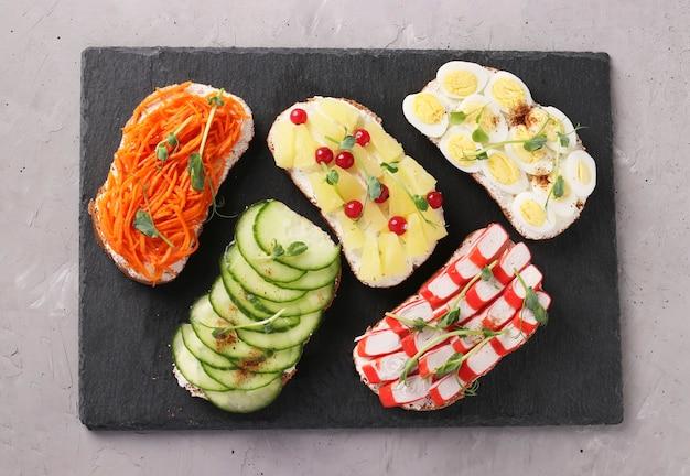 Пять бутербродов на тосте со свежей морковью, огурцами, ананасом, красной смородиной, крабовыми палочками и перепелиными яйцами с микрозеленью гороха на шиферной подставке на сером бетонном фоне. вид сверху