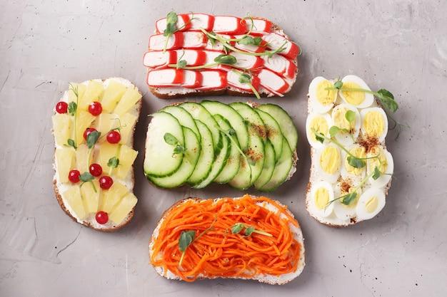 Пять бутербродов на тосте со свежей морковью, огурцами, ананасом, красной смородиной, крабовыми палочками и перепелиными яйцами с микрозеленью гороха на серой бетонной поверхности, вид сверху