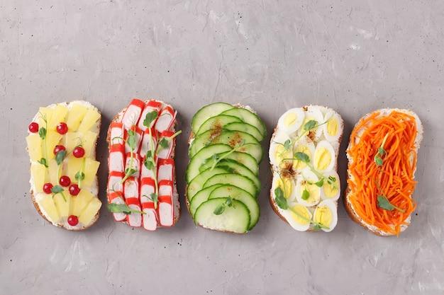Пять бутербродов на тосте со свежей морковью, огурцами, ананасом, красной смородиной, крабовыми палочками и перепелиными яйцами с микрозеленью гороха на серой поверхности