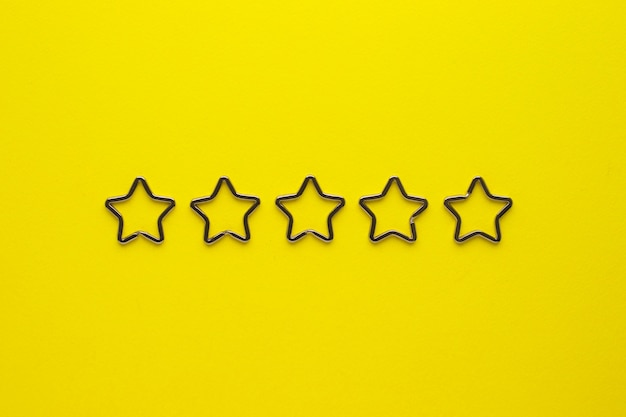 Пять блестящих металлических разрезных брелков в форме звезды для брелков. хромированная застежка-брелок на желтом фоне.