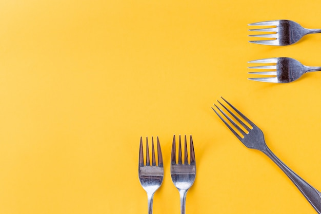 Five silver forks on yellow background