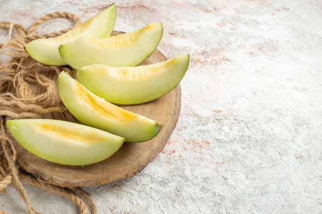 Five slices of melon on wooden platter and rope on left side of marble