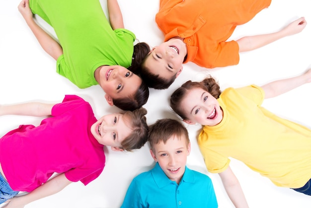 Five smiling children lying on the floor in a circle in bright t-shirts. top view. isolated on white.