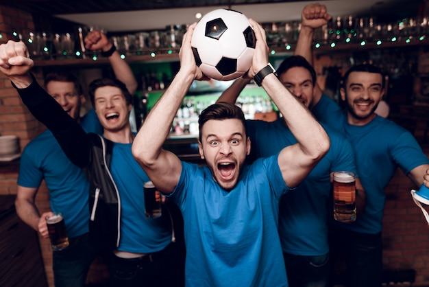 Five soccer fans drinking beer celebrating in bar.