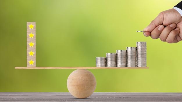 Пятизвездочный рейтинг на деревянном блоке с рукой клиента-бизнесмена, вкладывающей деньги в укладку монеты на балансировку качелей