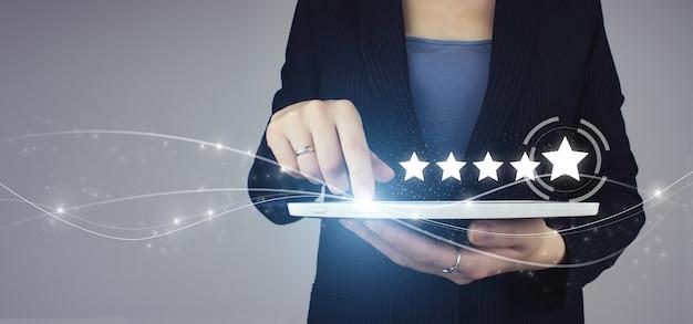 画面に触れる手で5つ星5の評価。灰色の背景にデジタルホログラム5つ星5評価記号と実業家の手の白いタブレット。