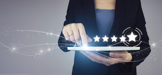 Five stars 5 rating with a hand touching screen. white tablet in businesswoman hand with digital hologram five stars 5 rating sign on grey background.