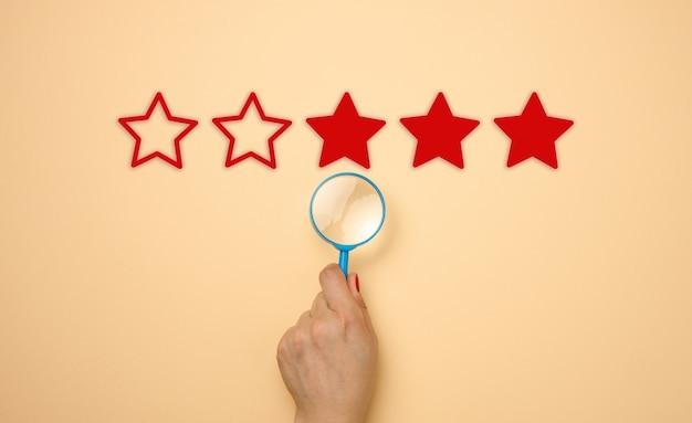 Пять звезд и рука с голубой пластиковой лупой на бежевом фоне. оценка качества услуг и товаров, высокий рейтинг