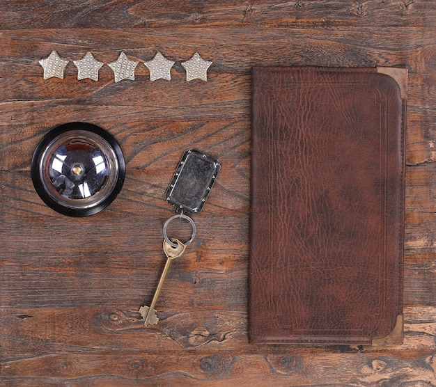 Five stars hotel service bell and hotel key on a wooden table