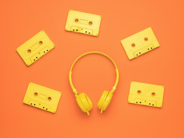 Five stylish yellow tape cassettes and yellow headphones on an orange background. color trend. vintage equipment for listening to music. flat lay.