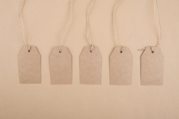 Five tags of recycled kraft paper fhanging from a rope on a kraft paper. flat lay