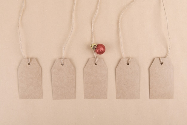Five tags of recycled kraft paper for packaging hanging from a rope decorated with a red christmas ball
