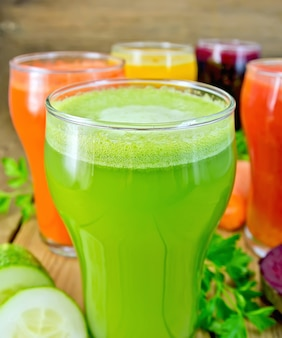 나무 판자 배경에 당근, 오이, 비트, 토마토, 호박, 야채, 파슬리 주스를 넣은 키 큰 유리잔 5개