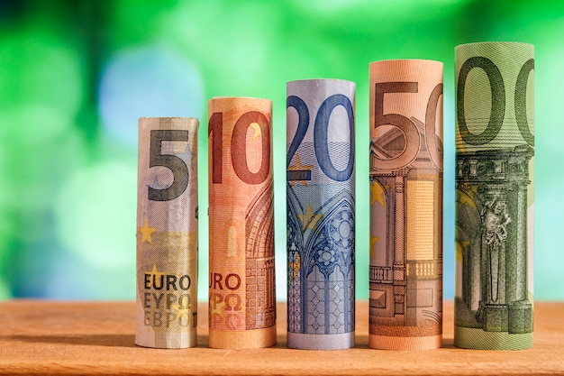 Five, ten, twenty, fifty and one hundred euro rolled bills banknotes on green blurred bokeh