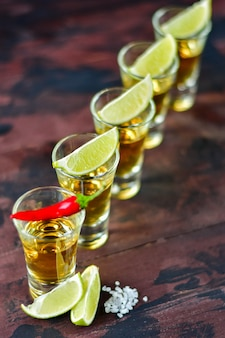 Five tequila shots with snacks lime and pistachio, salt and chili pepper for decoration, vodka, whisky, rum