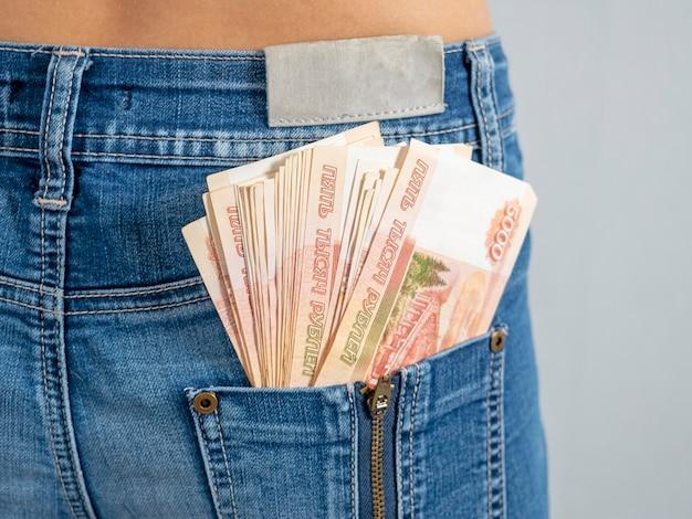 彼のジーンズの後ろのポケットに5000ルーブルの紙幣。あなたのポケットの中のお金の概念。現金。ロシアのお金