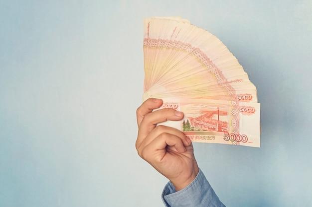 Пятитысячные купюры российских рублей в руке. наличные в виде веера. копировать пространство