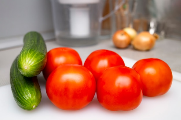 Five tomatoes, two cucumbers and an onion in the background in a real life kitchen, home production photography
