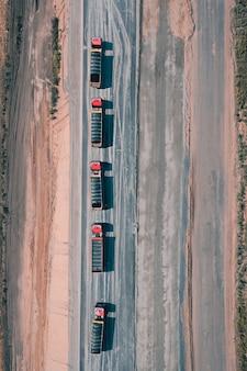 砂漠の空中ドローンショットの真ん中で、貨物を積んだ5台のトラックがアスファルト道路を走行しています