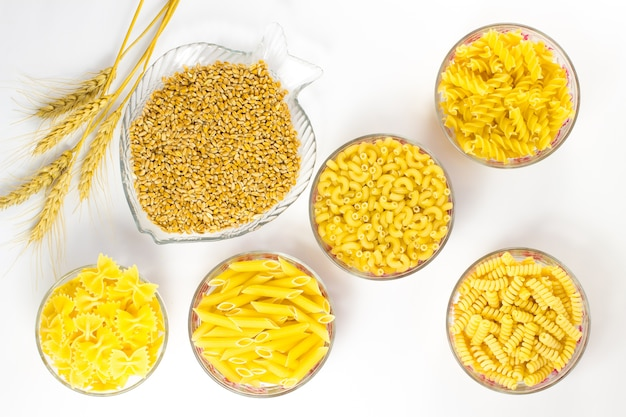Five types of pasta in glass plates. grains of wheat and wheat spikelets
