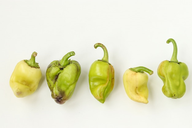 Five ugly organic bell pepper on white