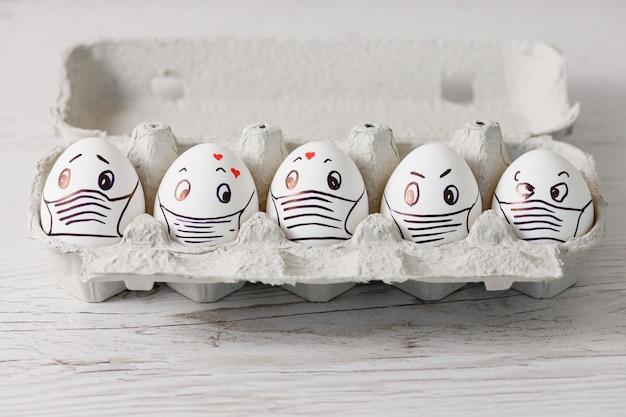 Пять белых яиц в подносе крупным планом с нарисованными эмоциональными глазами, сердечками и медицинской маской в связи с отменой праздника пасхи во время апрельского карантина по коронавирусу